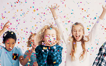 Happy group of kids having fun during birthday party with confetti
