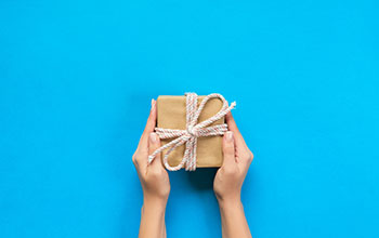Woman hands holding gift wrapped present in paper with ribbon.  The gift is in front of a blue background