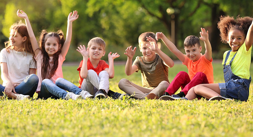 Cute little children sitting on grass with hands in the air outdoors on sunny day